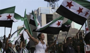 Protesters shout slogans against Syria's President Bashar al-Assad as they wave Syrian opposition flags during a protest marking two years since the start of the uprising, at Avenida Paulista in Sao Paulo March 15, 2013. REUTERS/Nacho Doce
