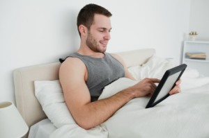man-watching-tablet-in-bed1-460x306
